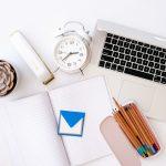 notebook pencils laptop clock stapler plant desk