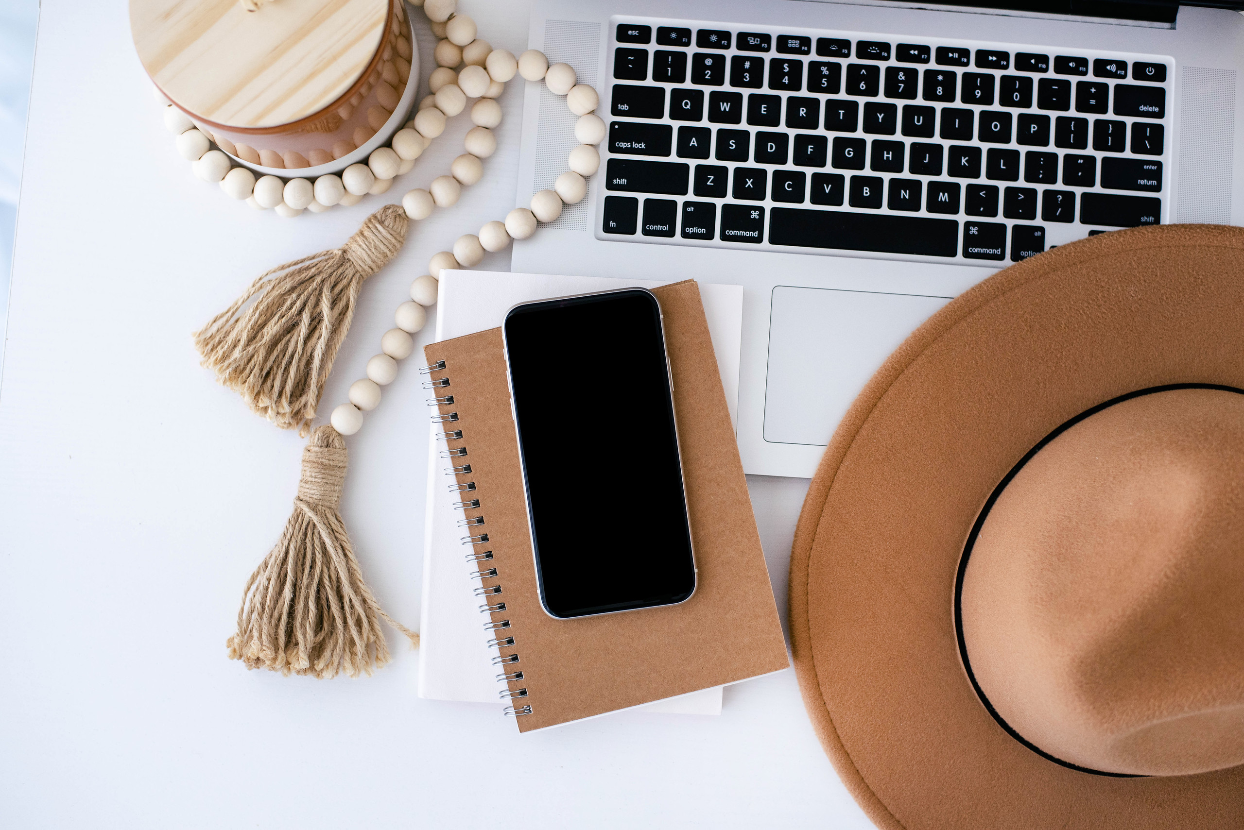brown hat, notebook, beads, phone, laptop