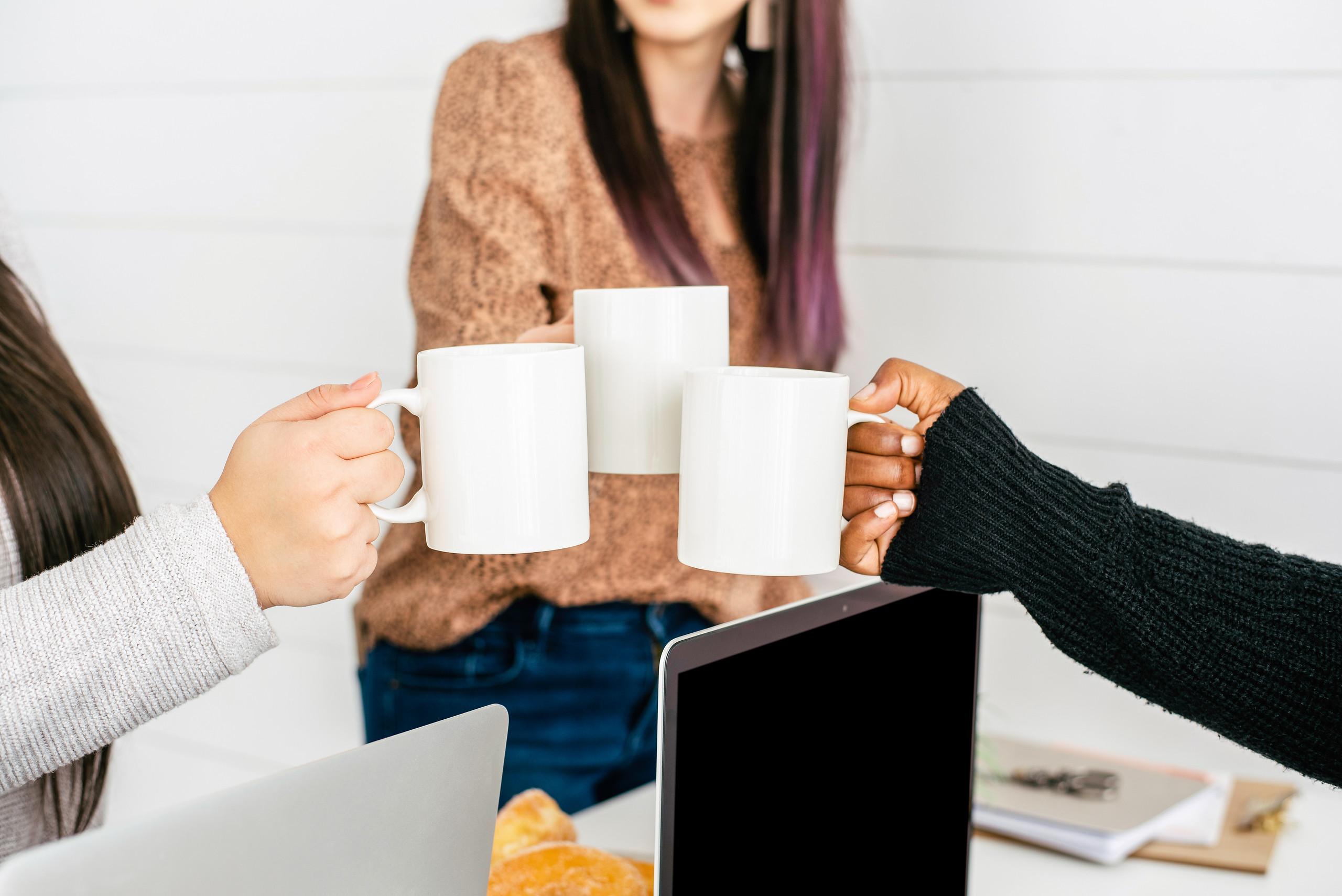 female friends holding coffee mugs