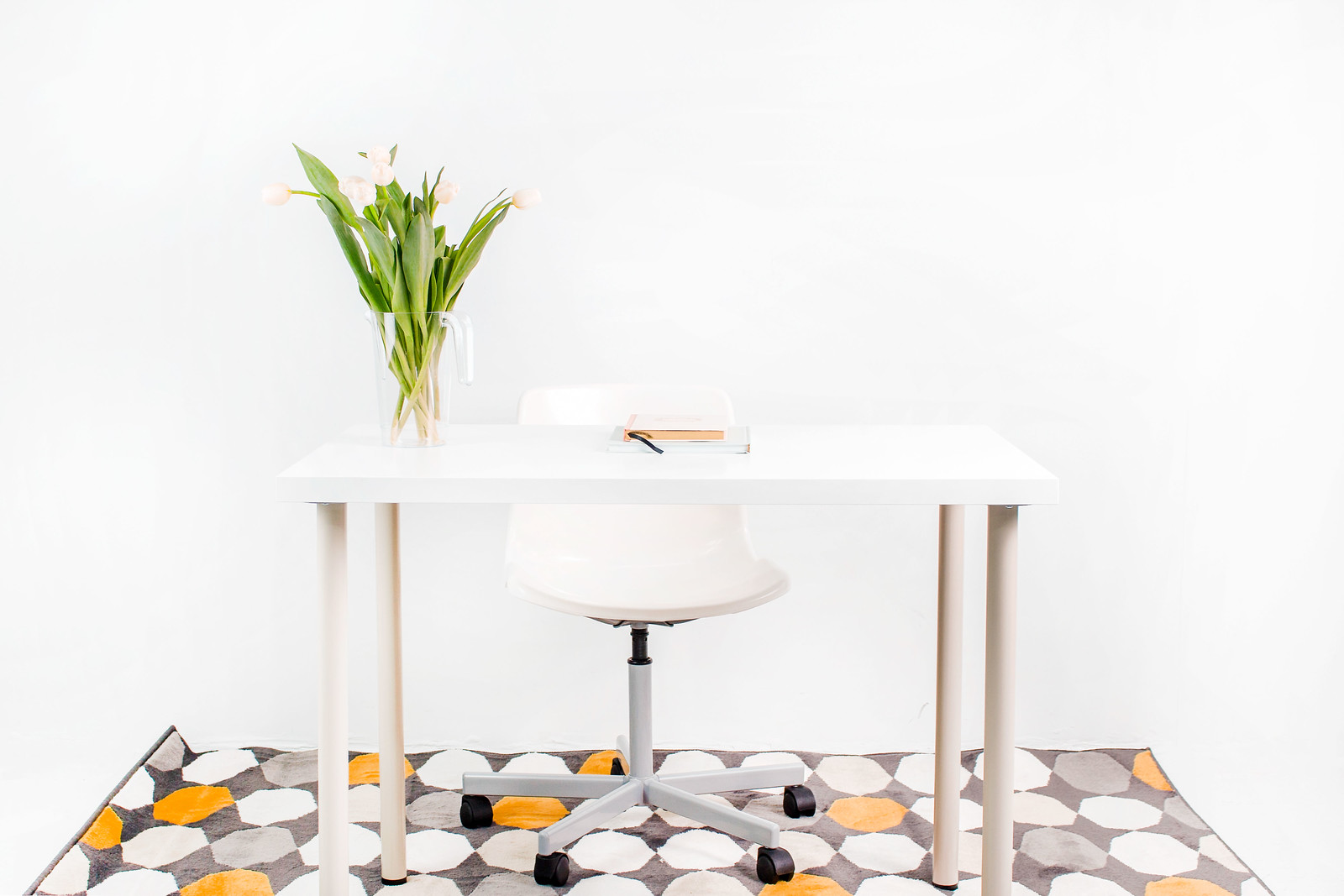 white desk, chair, flowers, notebooks, and gray, orange, and white circles on a mat