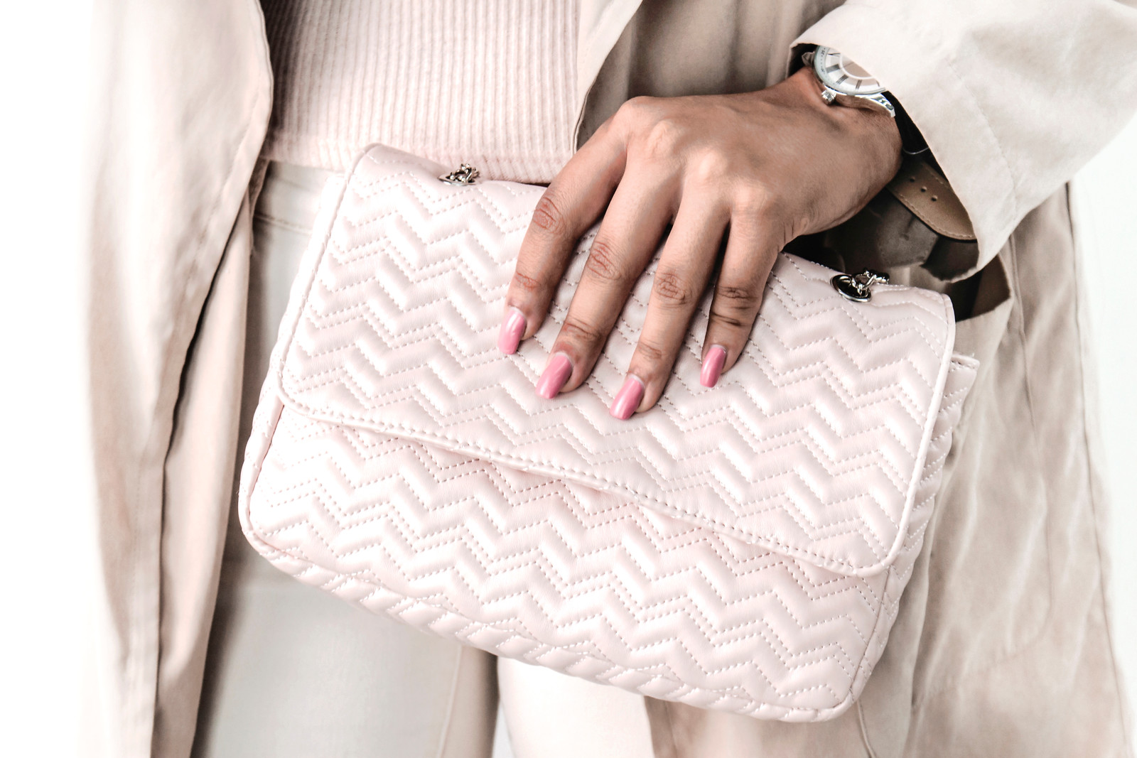 businesswoman wearing beige clothing and holding a pink purse