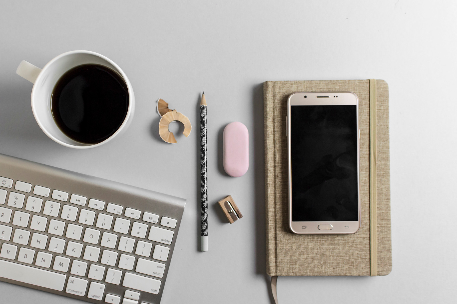 gray desk brown phone and notebook coffee keyboard pencil sharpener eraser