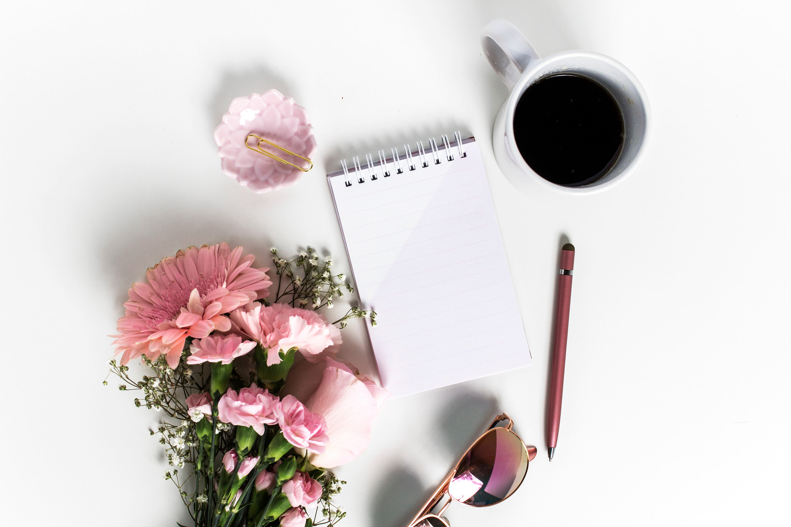 pink flowers, notepad, pen, sunglasses, cup of coffee