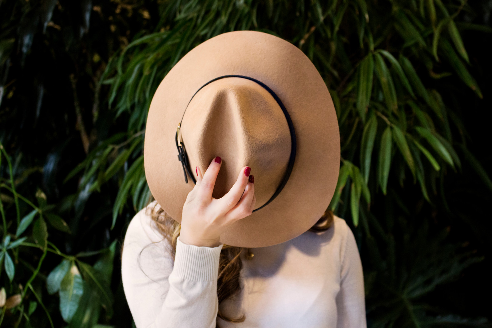 woman holding a brown hat